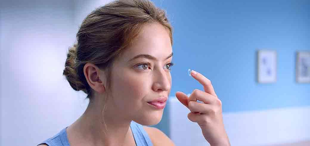 Hình ảnh của người phụ nữ đang đeo kính áp tròng vào mắt